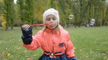 Happy little girl playing wit soap bubbles in autumn park, kids lifestyle