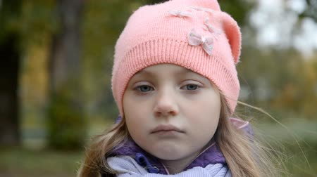 tek başına : Portrait of a sad girl who is 5 years old against the background of the city autumn park in a pink hat Stok Video