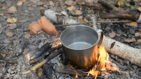 panelas : Cooking on a camping trip, water in a cup and charcoal sausages, food for the traveler