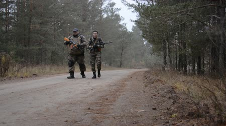commando : two men armed with Kalashnikovs mashine guns walk along a forest road on a cloudy autumn day Stock Footage