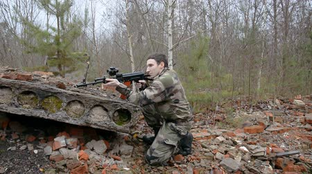 golyó : A soldier in ruins with a assault rifle aims at the enemy hd stock footage