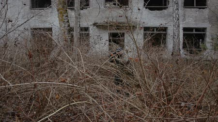 harcos : Two soldiers make their way through the bushes against the backdrop of an abandoned two-story building hd stock footage