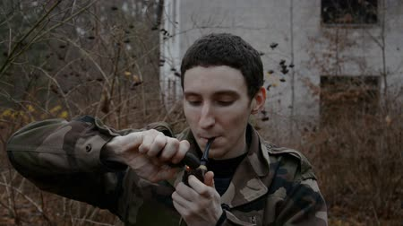 armas : Russian soldier smokes a tobacco pipe against the background of an abandoned building in the autumn forest