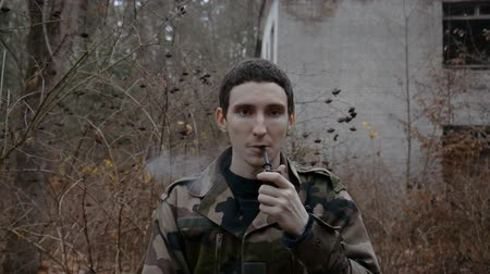 portrait of a young soldier who is smoking a tobacco pipe on the background of an abandoned building in the autumn forest