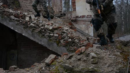 golyó : Two Russian soldiers descend the stairs of the destroyed building, military concept Stock mozgókép