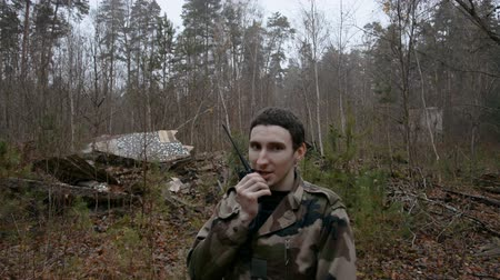 patrol : young soldier talking on the walkie-talkie in the autumn forest, military concept