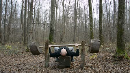 szörnyszülött : Exercising in the spring forest, lifting the bar, training in the fresh air hd stock footage
