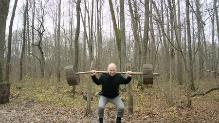 súlyzó : The guy is sitting with a barbell in the forest, sports concept