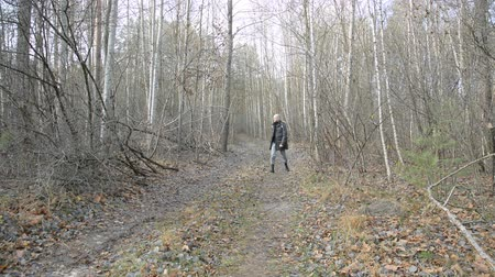 Hiker hiking in autumn forest, front view