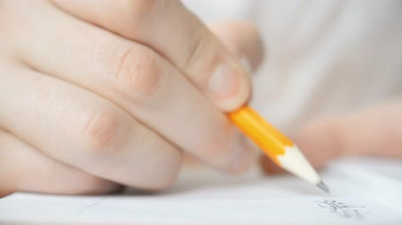 escrever : Pencil makes a note in Chinese in a notebook close-up hd stock footage