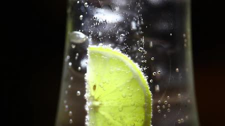 lemoniada : Color footage of a slice of lemon in a glass of soda, with ice cubes. Wideo