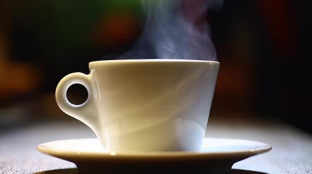 xícara de café : Color footage of a coffee mug put on a plate, with steam.