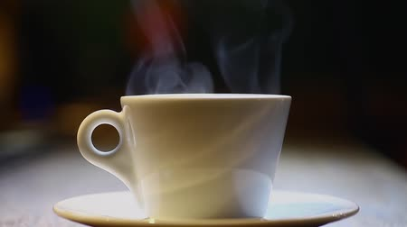 bögre : Color footage of a coffee mug put on a plate, with steam.