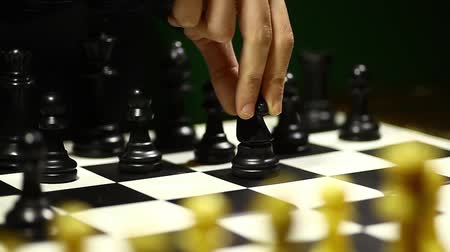 стратегический : Arrangement of black chess pieces on chess board, with horse moving.