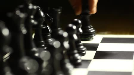 estratégico : Arrangement of black chess pieces on chess board, with pawn moving.