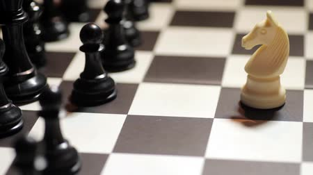 estratégico : Color footage of a chess match, with white knight facing black pieces. Stock Footage