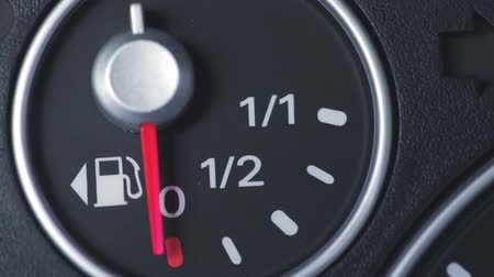 petrol : Color close up footage of a cars fuel gauge with the needle moving.