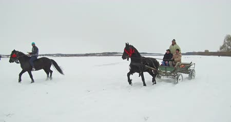 epiphany : Pietrosani, Romania - January 6, 2017: People ride horses or in carts on a snowy field, before a traditional Epiphany horse race in Pietrosani, Romania.