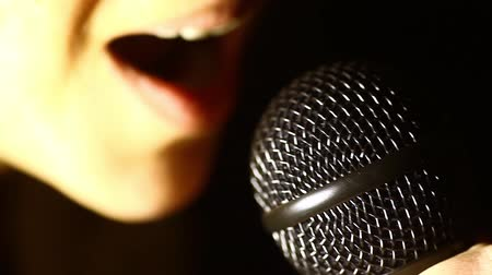 mikrofon : Close up footage of a woman singing to a microphone.