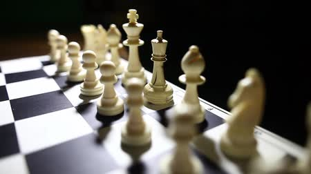 estratégico : Dolly push video of the white pieces on a chess board, with shallow depth of field. Stock Footage