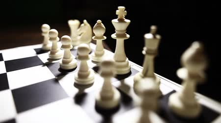 estratégico : Dolly pull video of the white pieces on a chess board, with shallow depth of field. Stock Footage