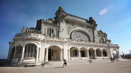 architectural heritage : Constanta, Romania - June 10, 2018: Footage of the abandoned casino in Constanta, Romania, with people walking by.