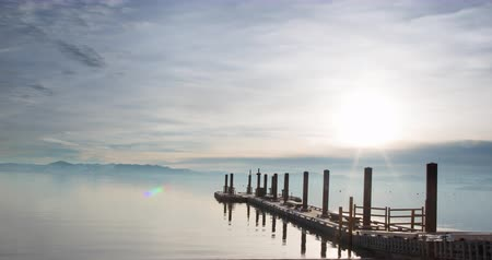 télen : Sunset Landscape. Reflection lake with pier and a view towards the horizon. Footage from Lake Tahoe, California.