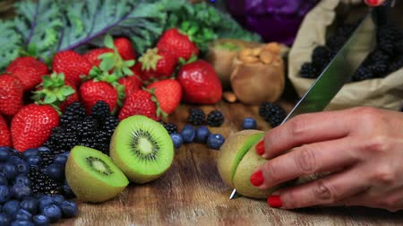 Cutting Kiwi on a Wooden Table Filled with Fresh Fruits