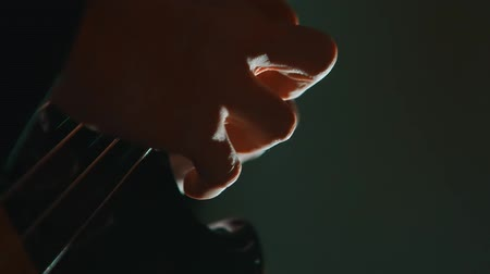 húr : Close-up of guitar playing. Guitarist hits the strings of the guitar.