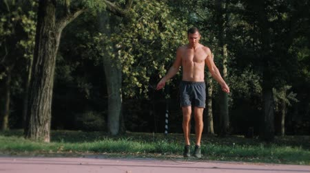 Young athletic man skipping with a jump rope outdoors in the park in slow motion