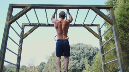 Strong athlete doing pull-up on horizontal bar outdoors