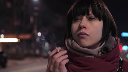 Woman smoking cigarette at the street