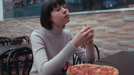 Young attractive woman eating pizza slice in pizzeria