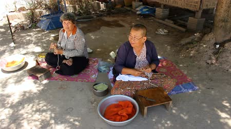 dokular : CAMBODIA - June 6, 2017: Two old Cambodian women sitting on the ground are working on the traditional textiles EDI MF Stok Video