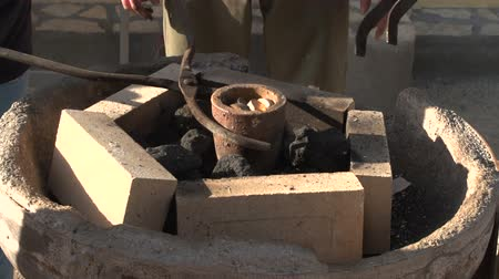 smithy : Positioning a melting pot in a forge with coking coals