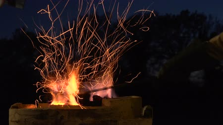 coals : Suggestive footage of many sparks in the night from a hot forge Stock Footage