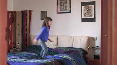 authenticity : Millennial candid child playing and jumping on bed