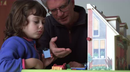 authenticity : Millennial candid child and dad playing with dollhouse Stock Footage