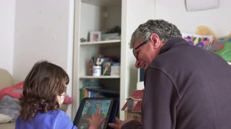 authenticity : Dad playing in real life on a tablet with daughter and adjoining