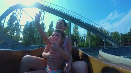 waterslide : Child and mother are greetings their friends on a slidewater Stock Footage