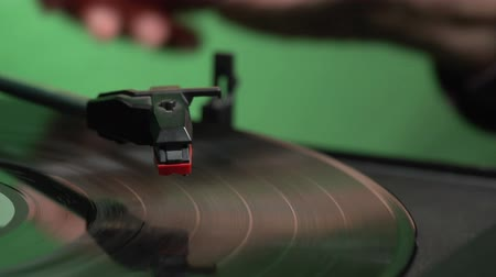 gramophone : Slow motion of hand stopping at vintage record player on green backgorund FDV