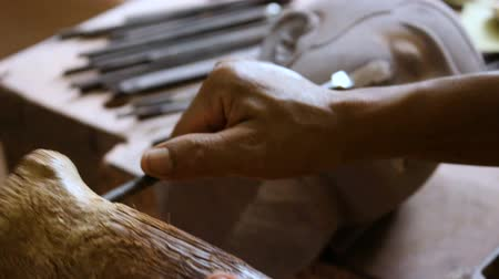cambojano : A cambodian artist is carving up a wood figure of buddha