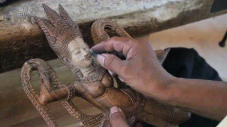 articles : An artisan is polishing a god figurine of wood. MF