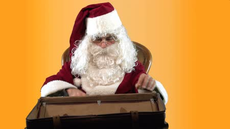 Santa Claus is looking for gifts in a vintage suitcase and finds old camera and clock. MF