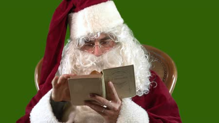 Santa Claus is reading an old book on a green background. MF Stock mozgókép