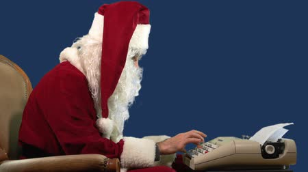 Santa Claus is writing a letter by an old vintage typewriter. MF