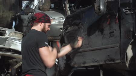 A young athlete is training by boxing on a car in a junkyard. FDV