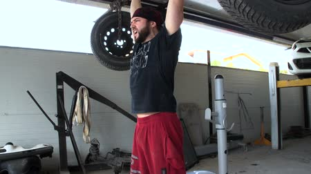 A strong athlete is training by weight with pneumatic tires in a junkyard. FDV