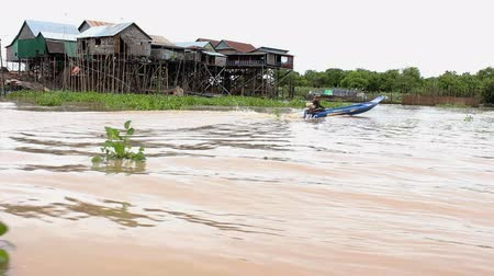 cambojano : A cambodian fisherman boat is on a big river with houses. MF