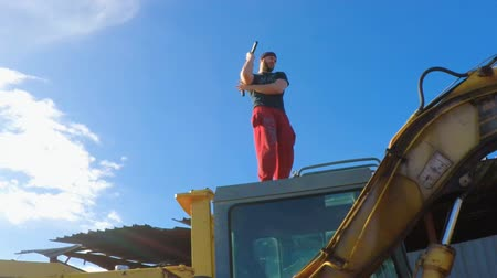A young athlete is training on a backhoe by Nunchaku on a blue sky FDV